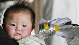 A baby evacuated from Fukushima Japan is measured for radioactivity.