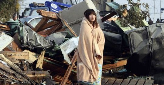 Shocked and homeless, a woman stares at the damage.